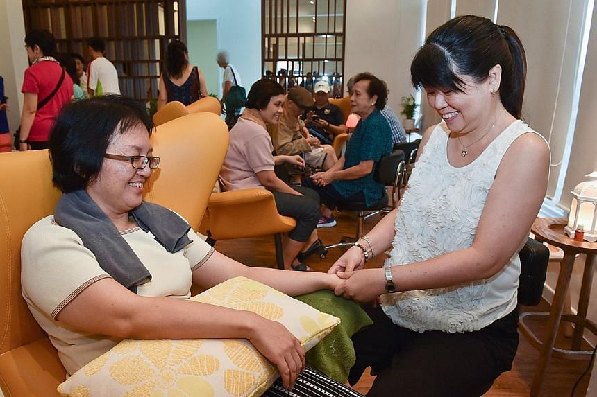 Ms Sally Low, whose chemotherapy treatment causes numbness in her hands, getting a massage from volunteer and freelance therapist Trinia Tjioe at the Yishun centre yesterday. Montfort Care programmes associate Chan Chiew Lan and volunteer Kalsom Abdu