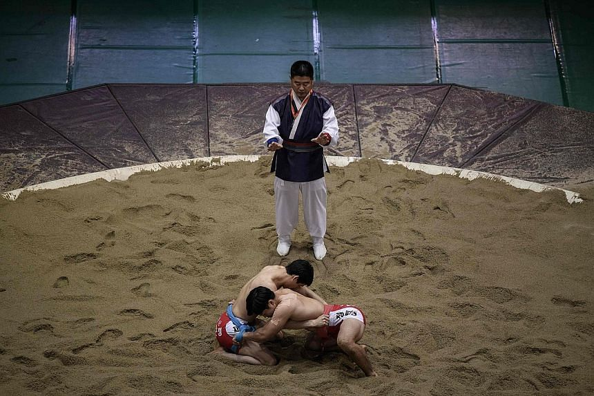 Ssireum wrestlers preparing to compete during the Korea Open Ssireum Festival last Monday in Andong, 190km south of Seoul. In South Korea, the wrestlers have their matches on sand, while in the North they use a round mattress.