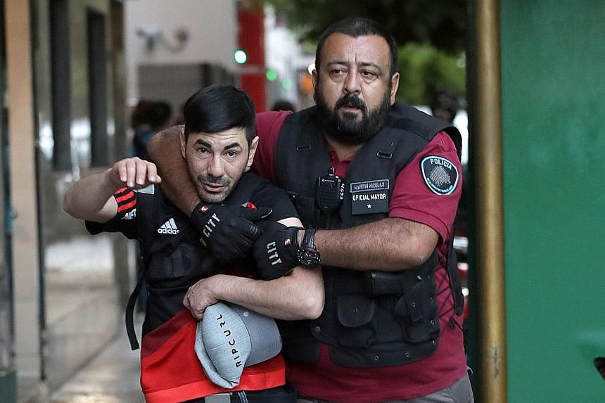 A River Plate fan being detained by a police officer.