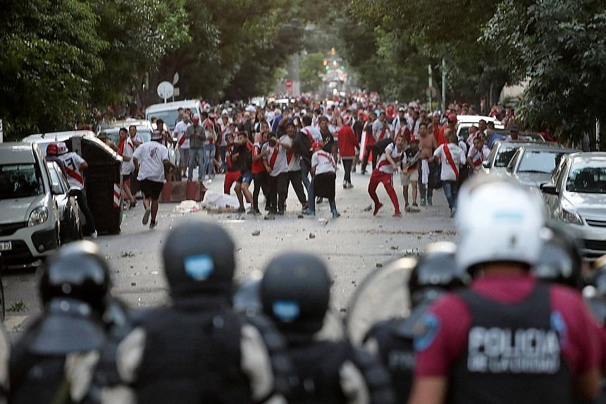 River Plate fans clashing with riot police after the second leg of the Copa Libertadores final against Boca Juniors on Saturday was postponed.