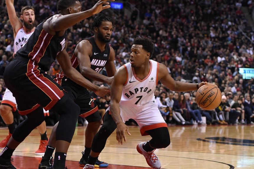 Toronto Raptors guard Kyle Lowry dribbles the ball away from Miami Heat forward Justise Winslow during their NBA game at Scotiabank Arena in Toronto on Nov 25, 2018.