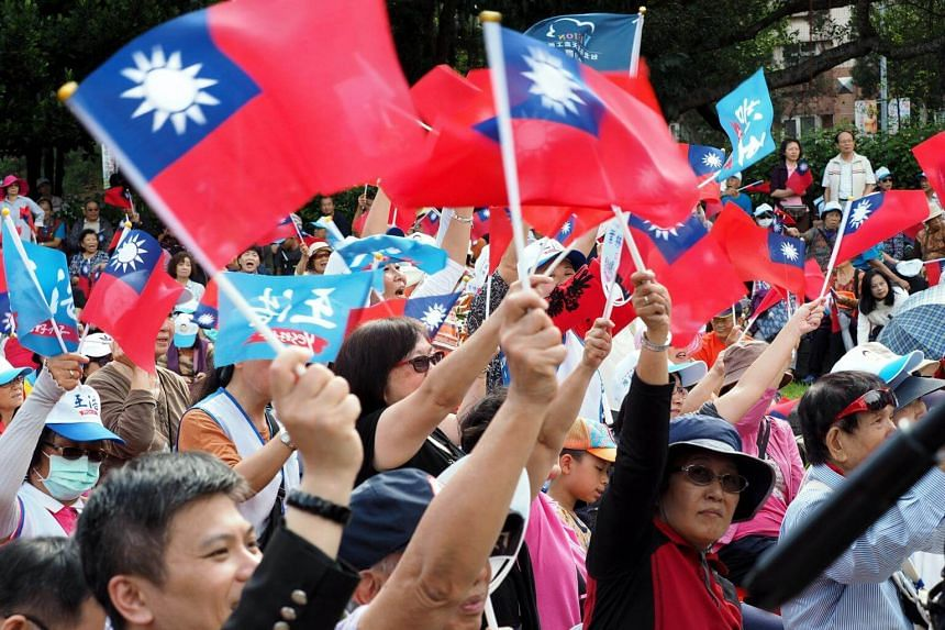 Opposition Kuomintang (KMT) Party supporters wave KMT flags at a campaign rally in Taipei, on Nov 18, 2018.