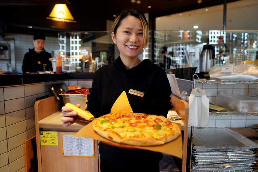 A waitress poses with a durian pizza at La Cesar Pizzaria in Shanghai, China, on Nov 2, 2018.