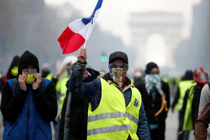 Masked protesters wearing yellow vests, a symbol of a French drivers' protest against higher fuel prices, take part in a demonstration on the Champs-Elysees in Paris, France, on Nov 24, 2018.