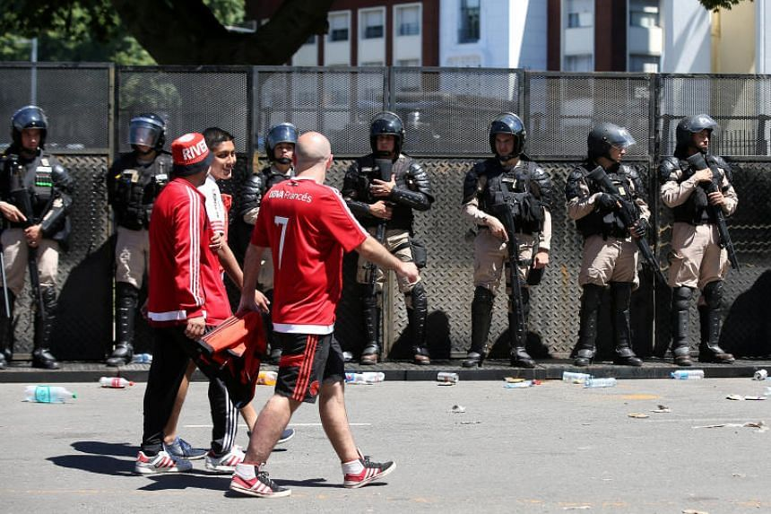 River Plate fans walk past police after the game between River Plate and Boca Juniors is postponed in Buenos Aires, Argentina, on Nov 25, 2018.