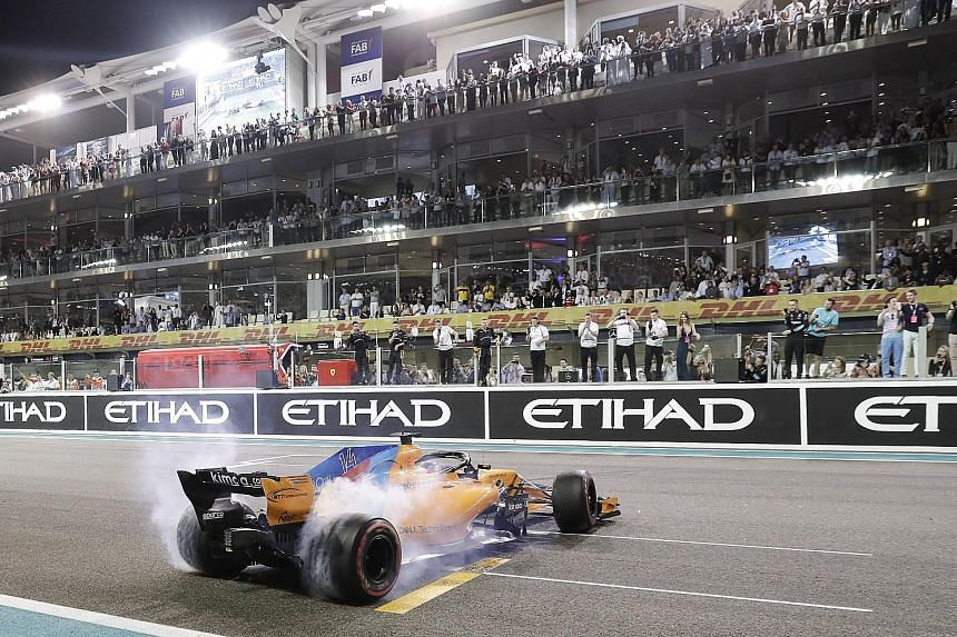 Fernando Alonso of McLaren performing a doughnut spin for thrilled fans after the Abu Dhabi Grand Prix at the Yas Marina Circuit on Sunday.