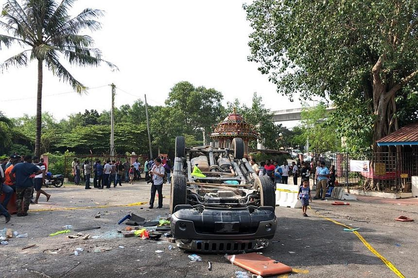 Above: It is believed that some 50 men entered the Sri Maha Mariamman temple in Subang Jaya at 2am yesterday and attacked those inside. Vehicles were torched during the clash. Below: Several men are seen overturning a vehicle at the temple in a scree
