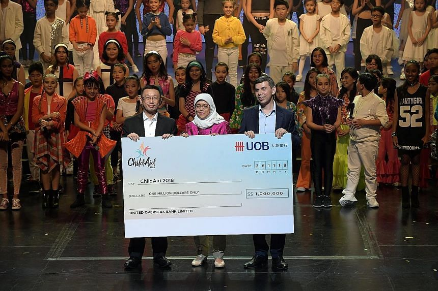 Far left: President Halimah Yacob witnessing the cheque presentation for UOB's donation of $1 million last night with UOB's Mr Choo Kee Siong (left), who is managing director and head of enterprise banking and commercial banking, and Mr Warren Fernan