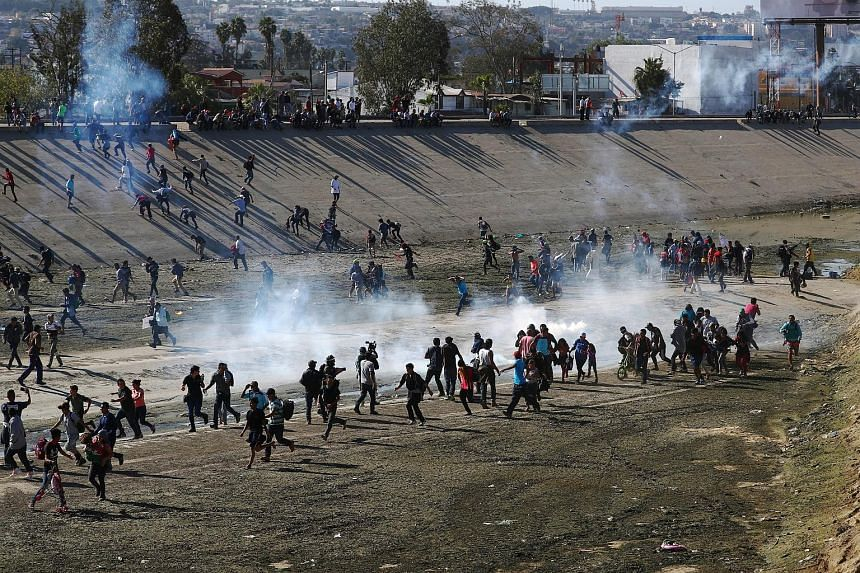 Above: Immigrants running from tear gas fired by the United States border patrol near the fence between Mexico and the US in Tijuana on Sunday. Left:Central American immigrants, mostly Hondurans, climbing a metal barrier on the Mexico-US border near