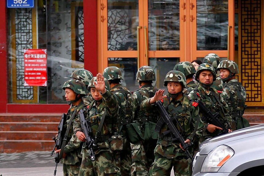 Paramilitary policemen stand guard in Urumqi, Xinjiang. Activists have protested Beijing over mass detentions and strict surveillance of the Muslim Uighur minority that live in the region.