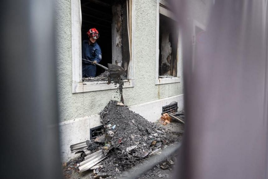 A forensic police officer inspects rubbles from a building where six people, including children, perished when a fire broke out in an apartment building in the northwestern Swiss town of Solothurn on early Nov 26, 2018.
