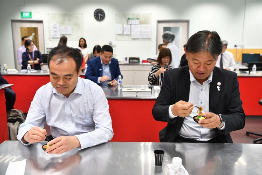 Deputy director-general of the Chinese Center for Disease Control and Prevention Li Xinhua (left) and Japanese Vice-Minister for Health Yasuhiro Suzuki sampling low-GI noodles at Singapore Polytechnic.