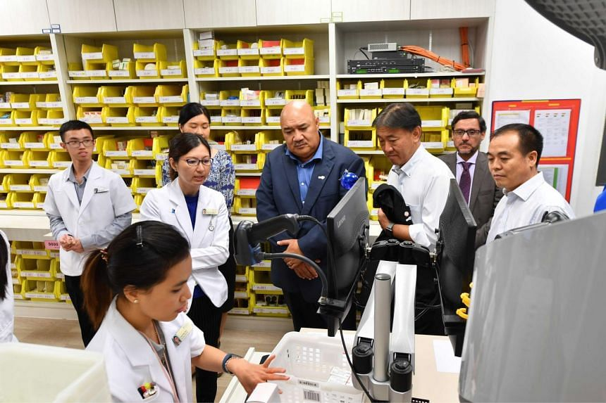 Delegates visiting the new Ang Mo Kio Polyclinic, where they observed the automatic medication dispensing system used in the pharmacy, on Nov 27, 2018.