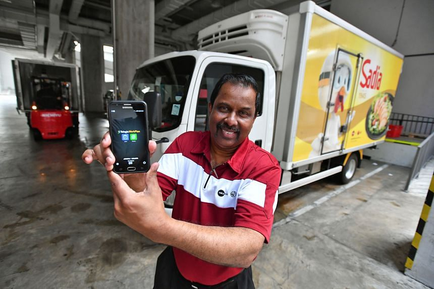 Transport supervisor Thavabala Krishnan showing the mobile app that he uses to automate the filing of delivery documents at Sats BRF Food. The app can reduce the time he spends on paperwork by 95 per cent.