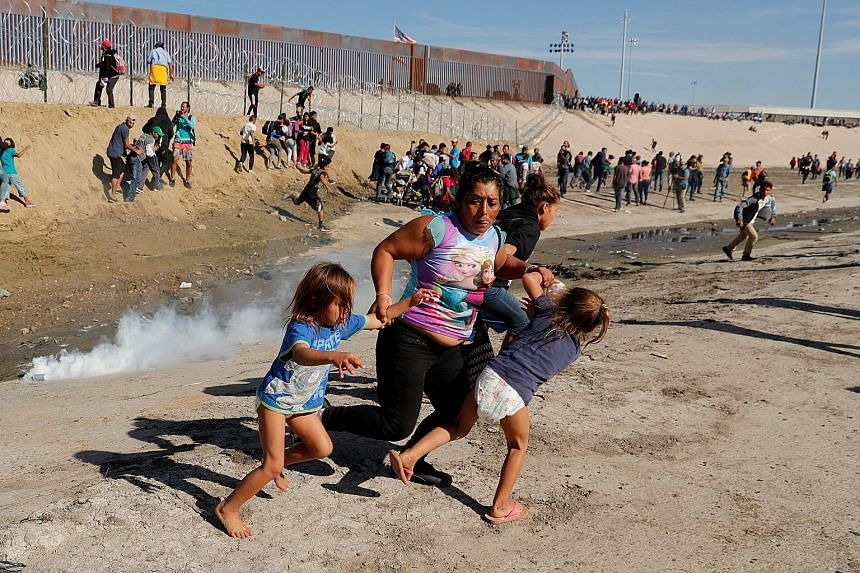 Ms Maria Lila Meza Castro, a 39-year-old migrant woman from Honduras, part of a caravan of thousands from Central America trying to reach the United States, running away from tear gas with her five-year-old twin daughters, Saira Nalleli Mejia Meza (l