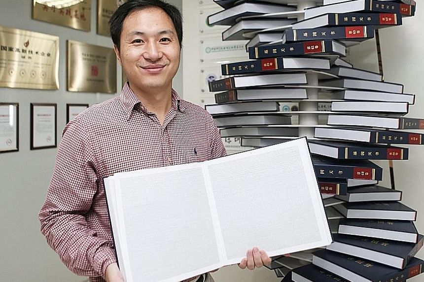 Chinese scientist He Jiankui at his company, Direct Genomics, in Shenzhen in China's Guangdong province in 2016. He is holding The Human Genome, a book that he edited. He has defended what he said he had achieved - embryonic gene editing to help prot