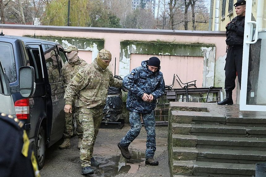 A detained Ukrainian navy sailor (at right) being escorted by a Russian security service officer before a court hearing in Simferopol, Crimea, yesterday. Moscow detained 24 sailors and seized three Ukrainian ships on Sunday, saying they illegally cro