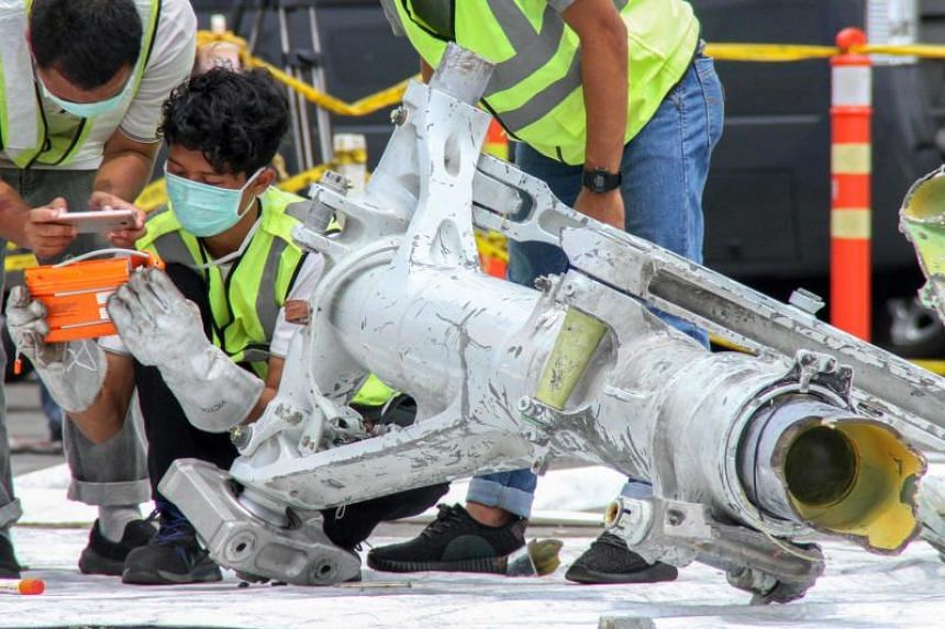 Lion Air investigators examine part of the landing gear of the ill-fated Lion Air Flight JT610 at the port in northern Jakarta.