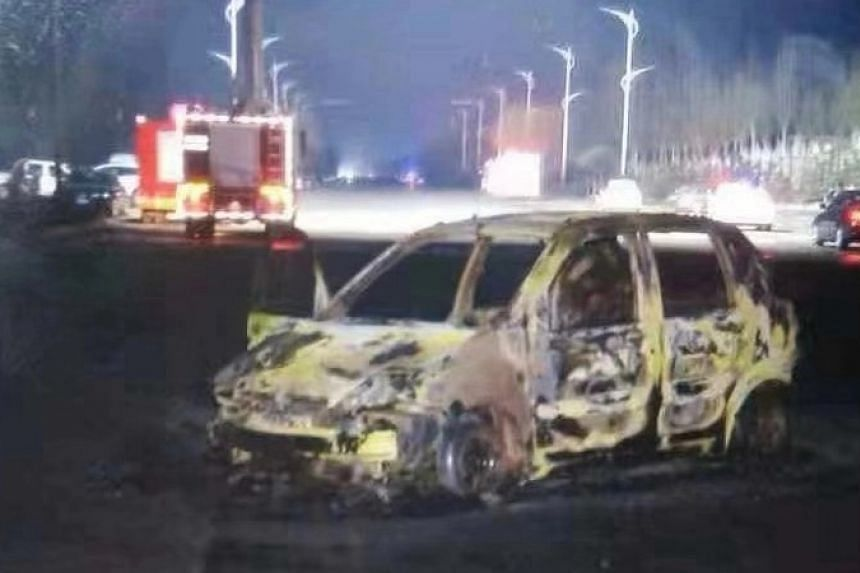 A charred car is seen on a road after an explosion and fire near a chemical factory in Zhangjiakou, on Nov 28.