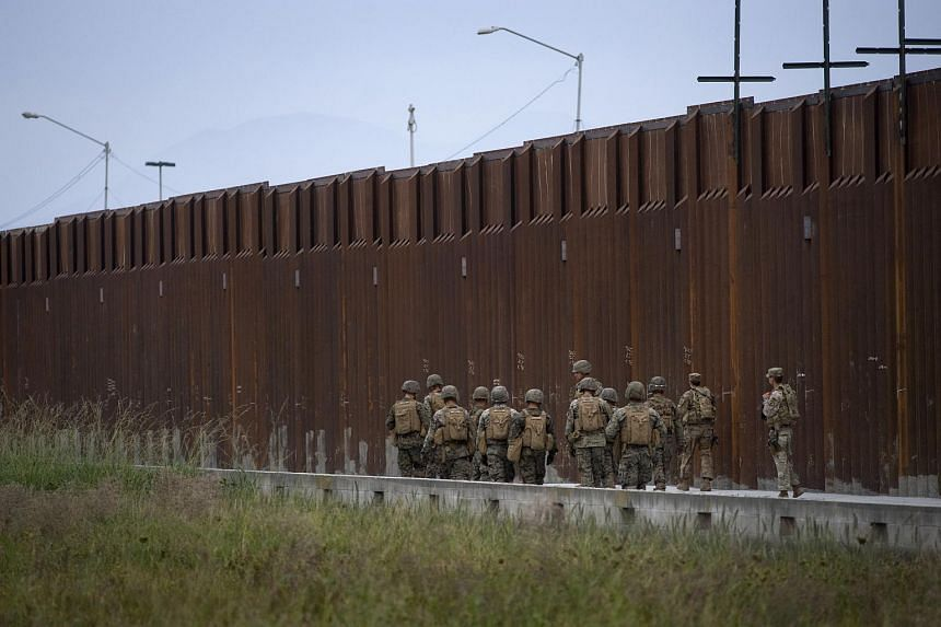 US military march next to the US-Mexico border wall near the Otay Mesa Port of Entry border crossing in San Diego, California.