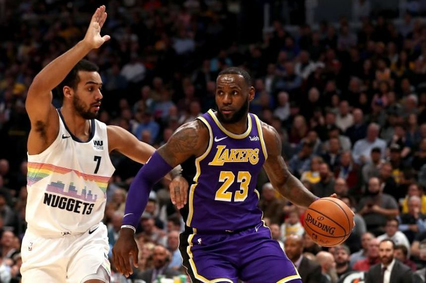 Lebron James of the Los Angeles Lakers (right) drives to the basket against Trey Lyles of the Denver Nuggets at the Pepsi Center in Denver, Colorado, on Nov 27, 2018.