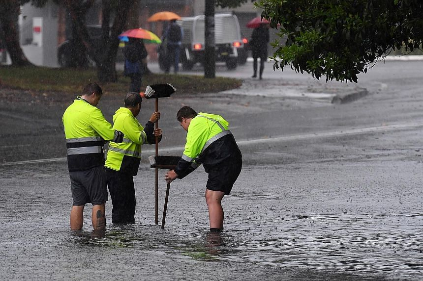 Council workers clearing a drain during rainy weather in Sydney, which received more than a month's worth of rain in just two hours yesterday.