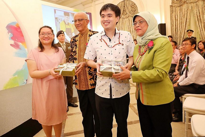 Metta Cafe apprentices Heng Shen, 26, and Shirley Heng, 28, presenting cookies to President Halimah Yacob and her husband, Mr Mohamed Abdullah Alhabshee, at the President's Challenge appreciation night at the Istana yesterday. Metta Welfare Associati