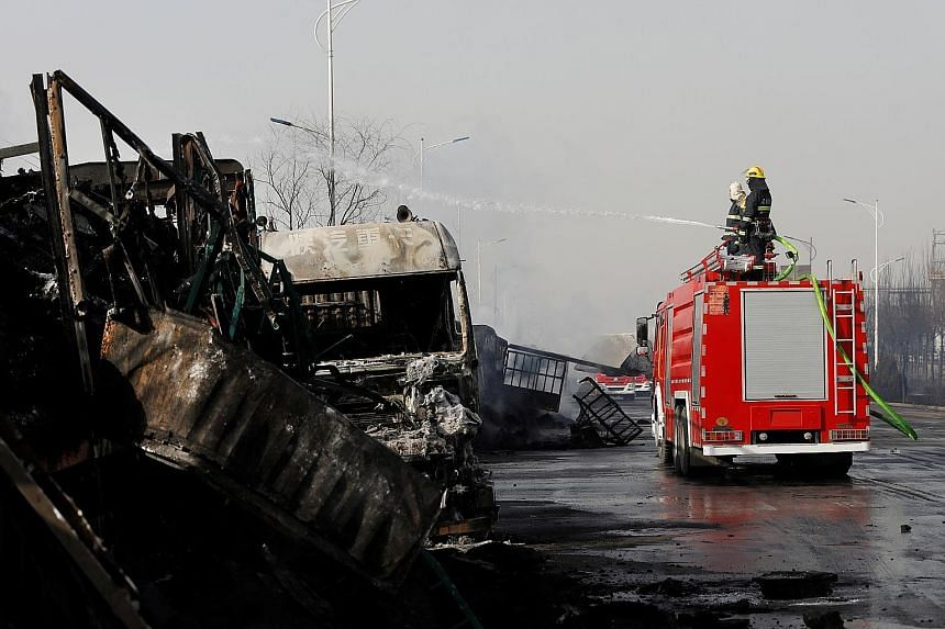 Firefighters work next to burnt vehicles following a blast yesterday near a chemical plant in Zhangjiakou, Hebei province, China. The country's authorities have vowed to improve industrial standards, but environmentalists fear oversight weaknesses st