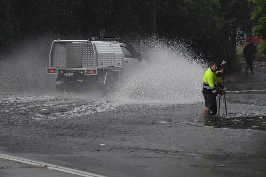 Workers trying to clear a drain, as a vehicle splashes through floodwaters on Railway Terrace during rainy weather in Sydney yesterday, when the city received more than a month's worth of rain in just two hours.