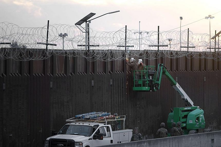 Troops helping US Customs and Border Protection to install concertina wire near the US-Mexico border wall near the Otay Mesa port of entry, in San Diego, California. The Democrats, who oppose the construction of a concrete barrier, have shown little