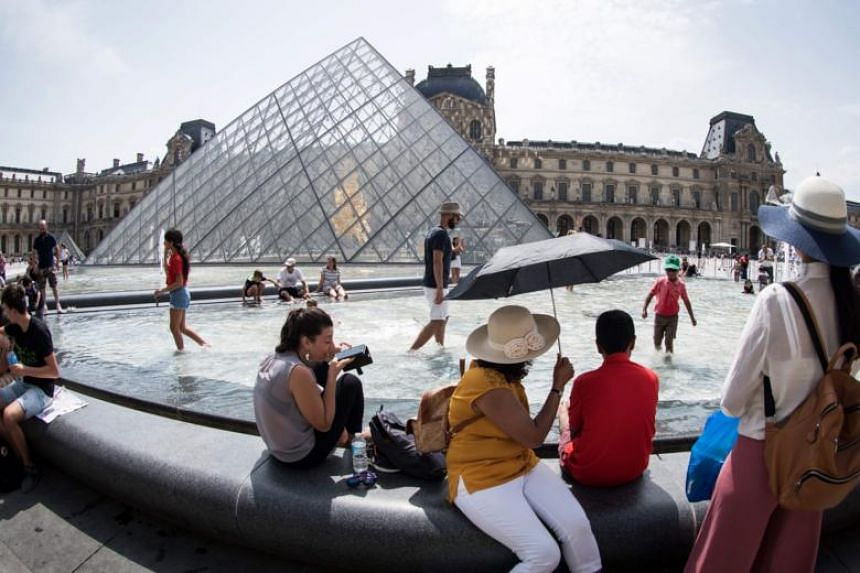 Tourists cool themselves at the fountain in front of the Louvre Pyramid in Paris during a heatwave in Europe, on Aug 7, 2018.
