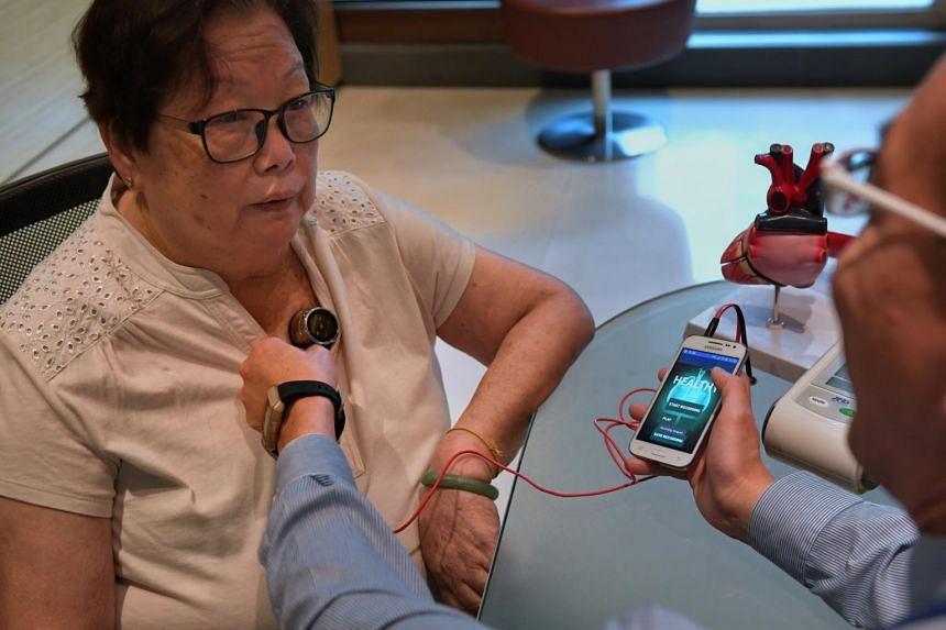 Associate Professor David Foo, the head of cardiology at Tan Tock Seng Hospital, demonstrates the home-use device to Madam Tan Hui Keng, a heart failure patient.
