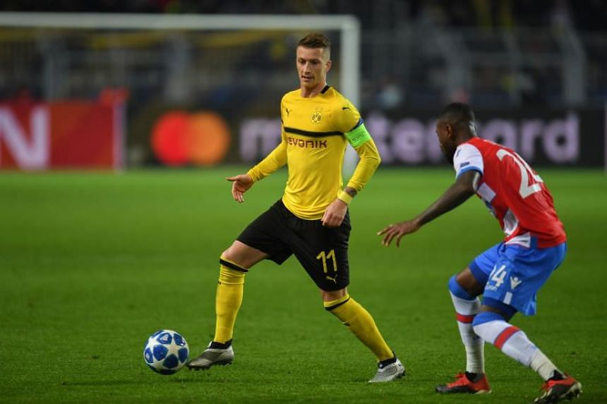Dortmund's German forward Marco Reus (left) and Club Brugge's Dutch defender Stefano Denswil vie for the ball during the UEFA Champions League group A match between BVB Borussia Dortmund and Club Brugge in Dortmund, western Germany on Nov 28, 2018.