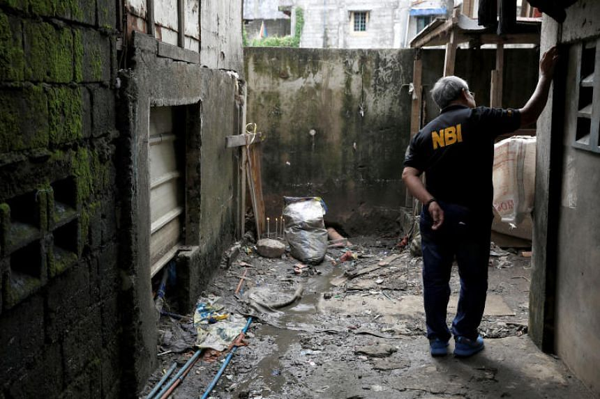 A member of the Philippine National Bureau of Investigation inspects the site where Kian delos Santos was killed during anti-drug operations in August 2017.