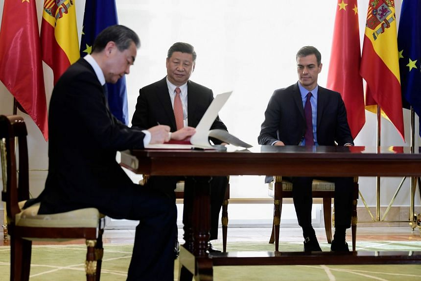Spanish PM Pedro Sanchez (left) and Chinese President Xi Jinping (centre) look at Chinese Foreign Minister Wang Yi as he signs agreements at the Moncloa Palace in Madrid, on Nov 28, 2018.