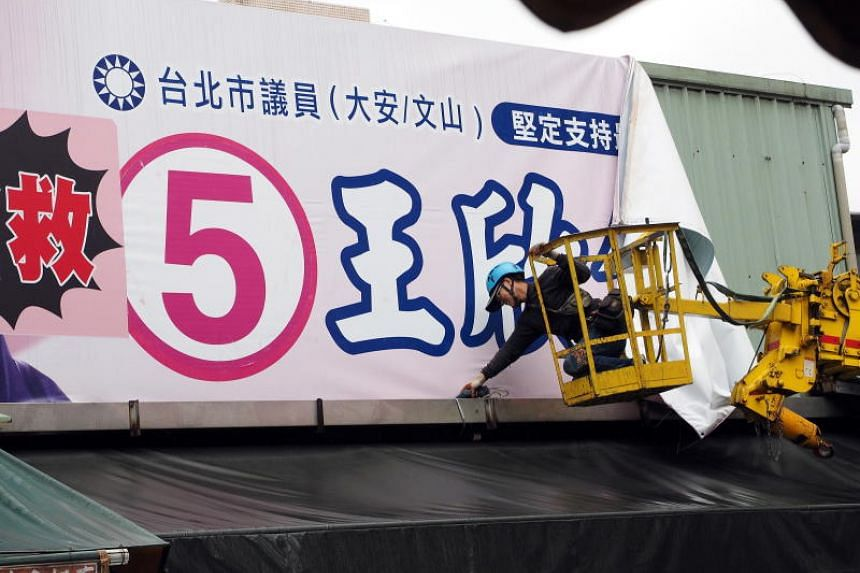 A worker removes a campaign banner from a building in Taipei, Taiwan, on Nov 26, 2018.