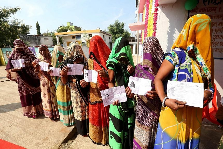 Some women in a village near Bhopal, India, showing their voting slips as they stand in a queue waiting to cast their votes in the Madhya Pradesh state assembly elections, which started on Wednesday. The state is ruled by the Bharatiya Janata Party.