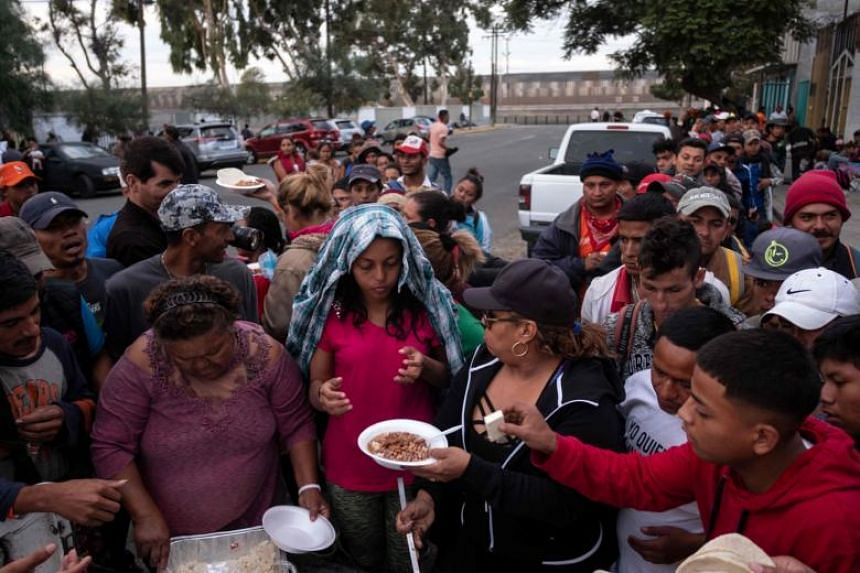 Central American migrants - mostly Hondurans - moving towards the US in hopes of a better life, line up for food outside a temporary shelter as the US-Mexico border fence is seen in the background, in Tijuana, Mexico, on Nov 15, 2018.