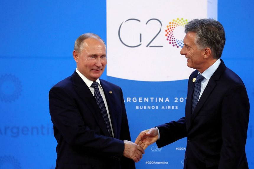 Argentinian President Mauricio Macri welcomes Russian President Vladimir Putin as he arrives for the Group of 20 leaders summit in Buenos Aires on Nov 30, 2018.