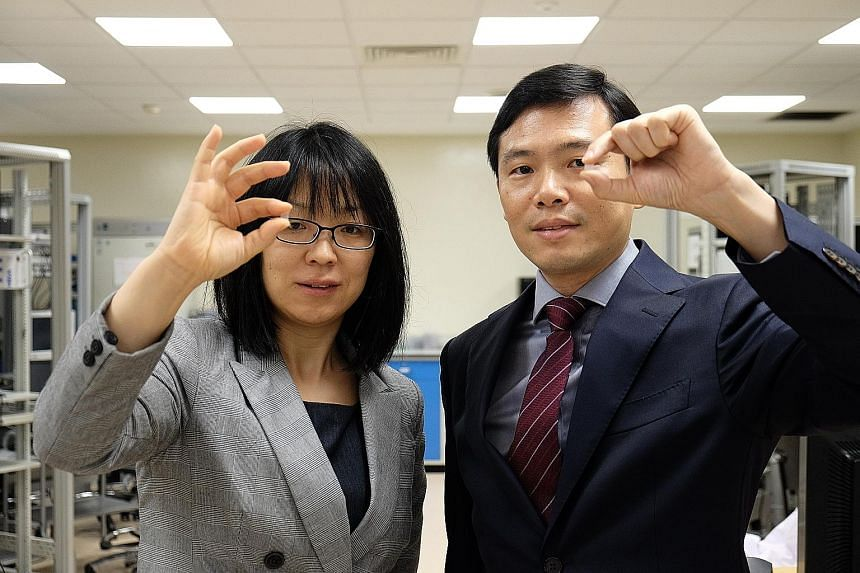 """Assistant Professor Wang Xiaomeng (left) and Professor Chen Peng with the """"contact lens"""" patch to treat eye diseases. Painless and minimally invasive, the patch could be a viable alternative to the current treatment options, which face poor patient c"""