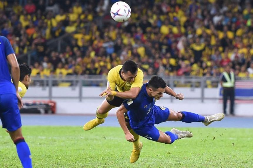 Malaysia's forward Norshahrul Idlan Talaha (left) and Thailand's defender Mika Chunuonsee fight for the ball during the first leg of the AFF Suzuki Cup 2018 semifinal football match between Malaysia and Thailand at the Bukit Jalil National Stadium in