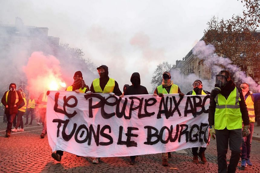 """Demonstrators hold a banner reading """"people in dire straits, let's kill the bourgeois"""" during a protest against rising oil prices and living costs on the Champs Elysees in Paris, on Dec 1, 2018."""