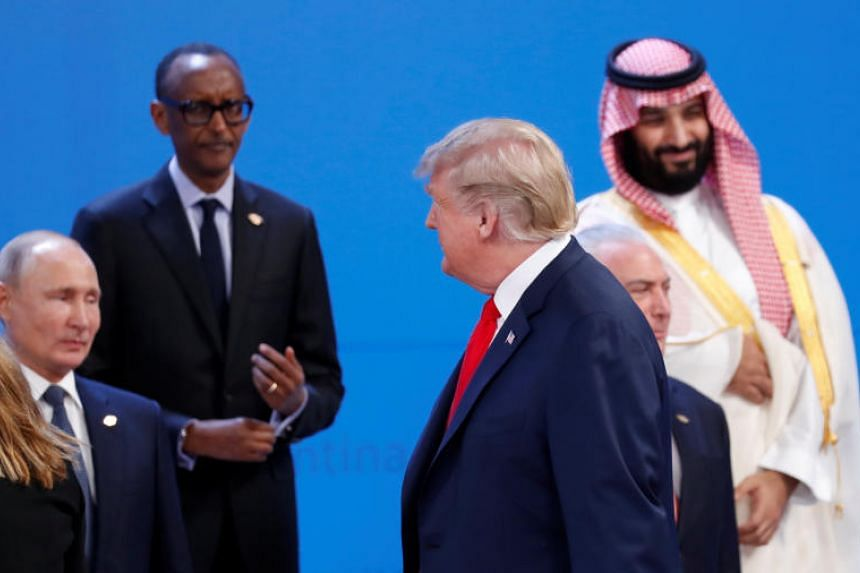 US President Donald Trump walks past Russia's President Vladimir Putin, Rwandan President and African Union chairperson Paul Kagame, Saudi Crown Prince Mohammed bin Salman and Brazil's President Michel Temer during the G-20 leaders summit in Buenos A