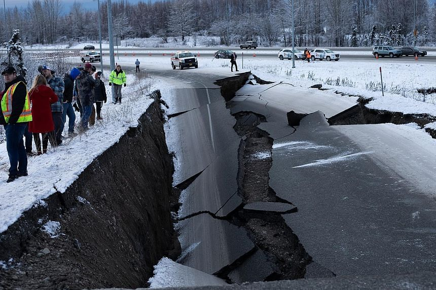 Road crew and residents surveyed the damage on the Minnesota Drive Expressway (above) while a stranded vehicle was pulled out of a collapsed section of roadway near the airport.