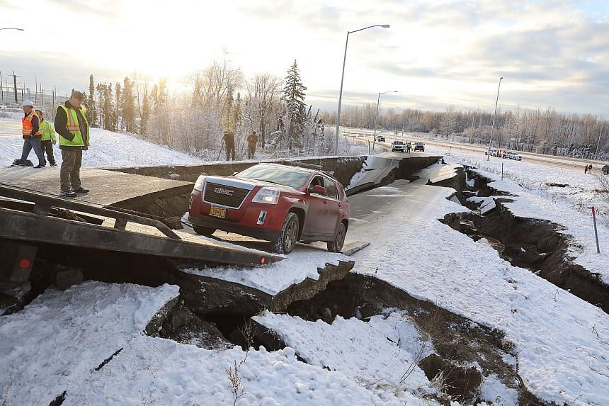 A magnitude-7 earthquake jolted southern Alaska on Friday morning, buckling roads and damaging buildings in Anchorage, the state's largest city. Road crew and residents surveyed the damage on the Minnesota Drive Expressway (above) while a stranded ve