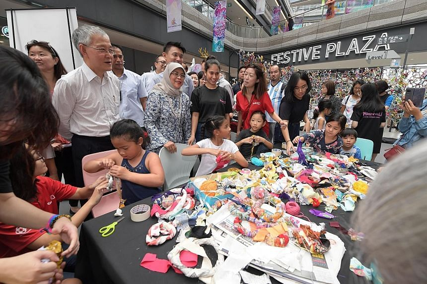 Top: President Halimah Yacob mingling with participants at an art-making session during the launching of the Creative Mindset Hub yesterday at Our Tampines Hub. Above: The President pledging her support to nominate Singapore's hawker culture for Unes