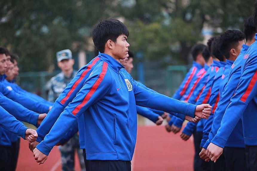 The Shanghai Shenhua U-19 football team marching, as a soldier looks on during a military-style training session at the team's training ground in Shanghai last week. Shenhua and China's national squad have sent young players off for military drills a
