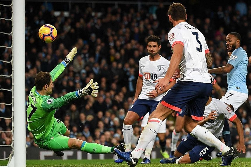 Raheem Sterling (right) putting Manchester City back ahead, 2-1, after 57 minutes in the Premier League game yesterday. Visiting Bournemouth had shocked their Etihad Stadium hosts with a Callum Wilson equaliser a minute before the break to cancel out