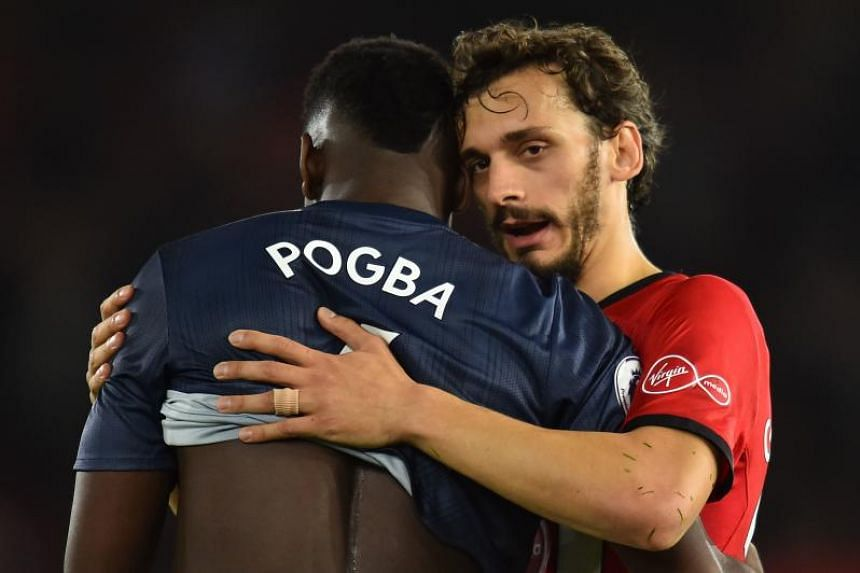 Manchester United's French midfielder Paul Pogba (left) is hugged by Southampton's Italian striker Manolo Gabbiadini during the English Premier League football match between Southampton and Manchester United at St Mary's Stadium in Southampton, south