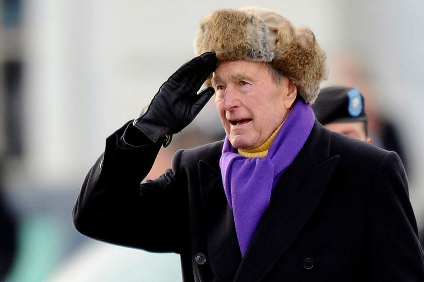 File photo of former US President George H. W. Bush saluting as he departs the East Front of the US Capitol Building, in January 2009.